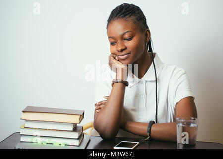 african young woman sitting at table with books at home - Stock Photo