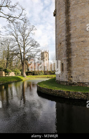Nunney Castle with the Church of All Saints in the background, Nunney, Somerset, England - Stock Photo