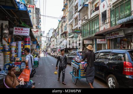 Few people and cars on a back street in downtown Yangon, Myanmar (Burma). - Stock Photo