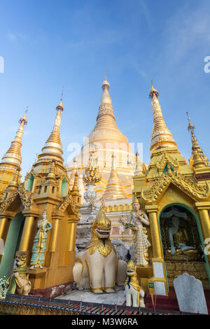 Small pagodas and statues in front of the gilded Shwedagon Pagoda in Yangon, Myanmar on a sunny day. - Stock Photo