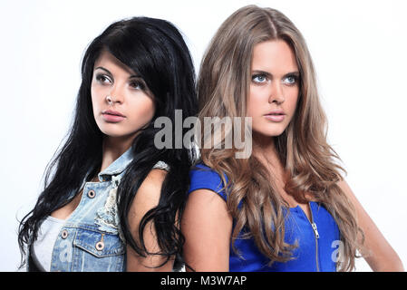 Two beautiful women standing back to back - Stock Photo