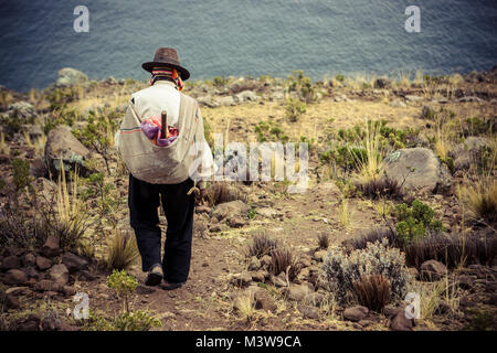 Poor man seen from behind walking down a cliff, Taquile Island, Titicaca lake, Peru - Stock Photo