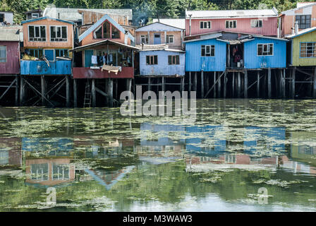Colorful wooden houses on stilts reflected in water on the island of Chiloe, Chile - Stock Photo