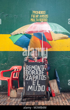 A mute man offering shoe repair on the street in Bogota, Colombia - Stock Photo