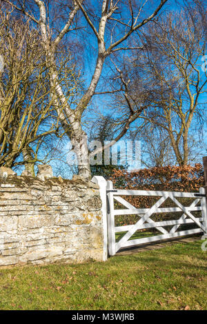 An ancient stone wall, ending with a traditional wooden bar gate, with bare trees in winter, against a clear blue - Stock Photo
