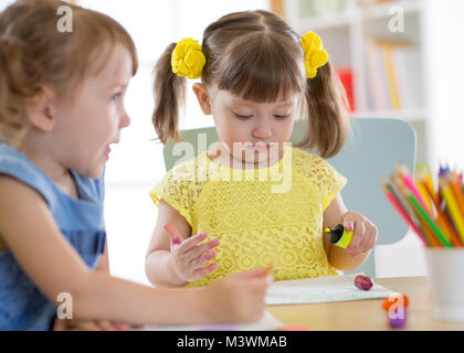 Kids drawing in kindergaten. Children paint in nursery. Preschooler with pencils at home. Creative toddlers. - Stock Photo