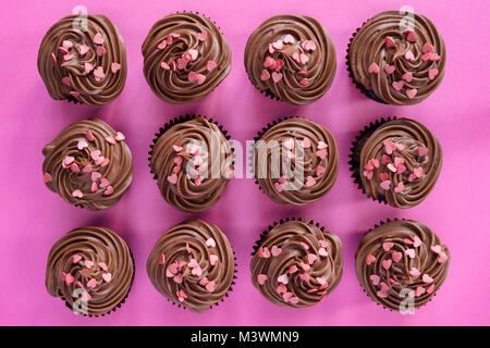Colourful chocolate cupcakes with heart shaped sprinkles on a pink background. Pattern - Stock Photo