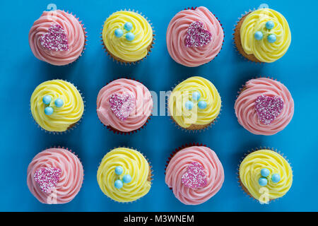Colourful yellow lemon and pink heart cupcakes on a blue background. Pattern - Stock Photo