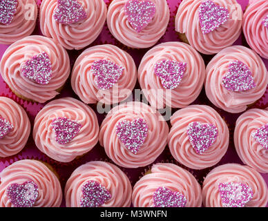 Colourful pink heart cupcakes on a pink background. Pattern - Stock Photo