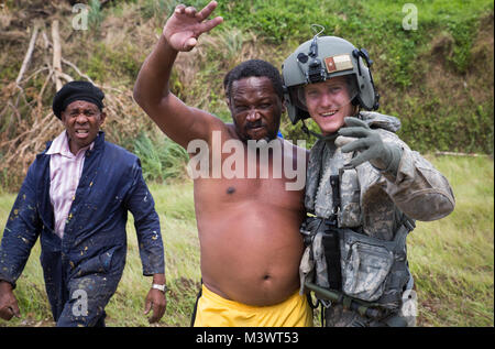 U.S. Army Sgt. Delton Reynolds, right, a flight engineer with Joint Task Force – Leeward Islands, hugs a local resident - Stock Photo