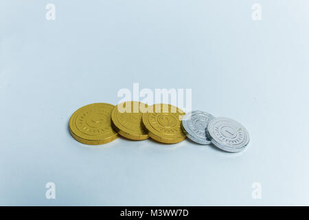 Gold and silver chocolate coins in wrappers. - Stock Photo