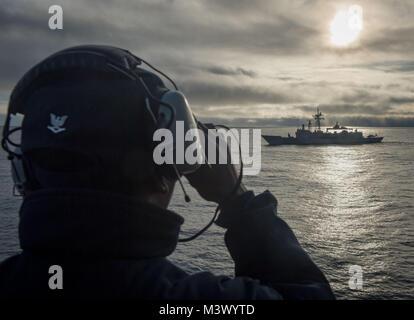 180121-N-RG482-251 ATLANTIC OCEAN (Jan. 21, 2018) Culinary Specialist 3rd Class Kadeem Wickham uses binoculars to - Stock Photo