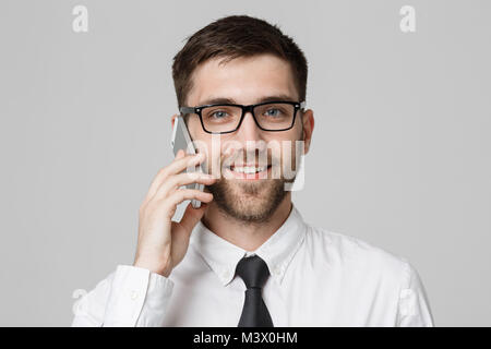 Business Concept - Portrait young handsome cheerful business man in suit talking on phone looking at camera. White - Stock Photo