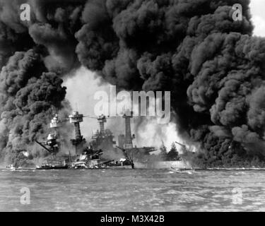 The U.S. Navy battleships USS West Virginia (BB-48) (sunken at left) and USS Tennessee (BB-43) shrouded in smoke - Stock Photo