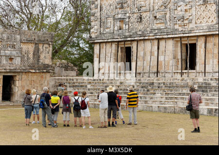 Group of tourists in the Nunnery Quadrangle at the Mayan ruins of Uxmal, Yucatan, Mexico - Stock Photo
