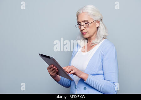 Portrait  of pretty, charming, aged woman with holding tablet, using wifi internet for work, checking email, standing - Stock Photo