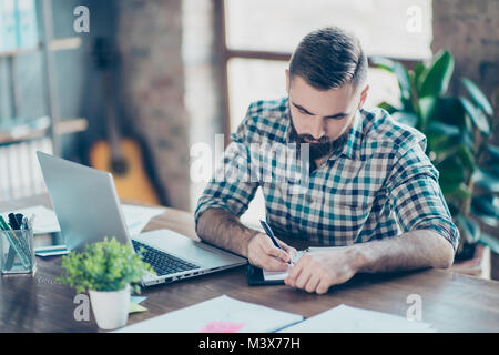 Attentive smart clever intelligent male student wearing checkered shirt is doing homework at home in front of modern - Stock Photo