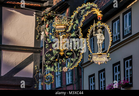 Wrought-iron sign at cafe Zum Roland, Breite Strasse at Altstadt in Quedlinburg, Saxony-Anhalt, Germany - Stock Photo