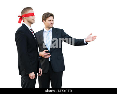 Confident Young Businessman Assisting Blindfolded Partner On White Background - Stock Photo