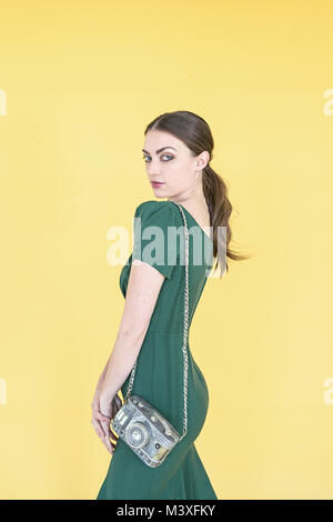 A portrait of a beautiful girl wearing a green dressed posing with a hand bag that looks like a camera- isolated - Stock Photo