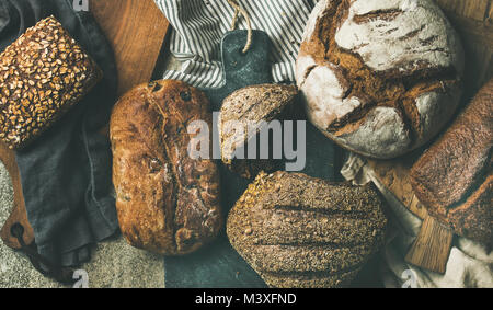 Flat-lay of various bread loaves, top view, wide composition - Stock Photo