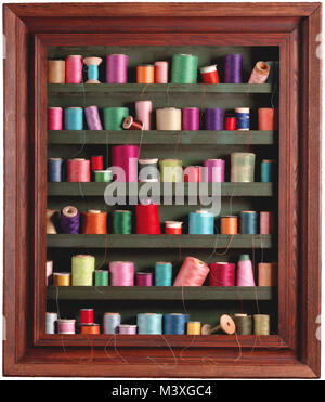 Sewing spools in frame, vertical color photograph of various vintage, spools in a vertical color studio photograph, - Stock Photo