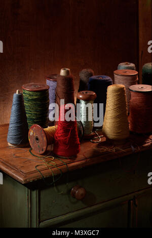 Multiple weaving spools with cotton or wool thread on them.  Vertical color photograph shot in a studio setting - Stock Photo