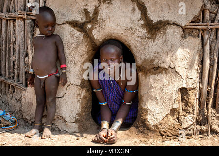 Portrait of Mursi mother with son near their hut with a small entrance - Ethiopia. © Antonio Ciufo - Stock Photo