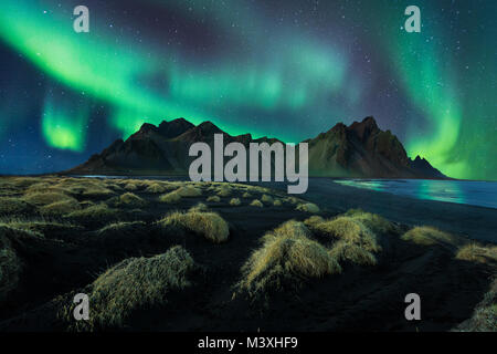 Iceland night landscape amazing northern light in vestrahorn mountain with black sand dunes at stokksnes - Stock Photo
