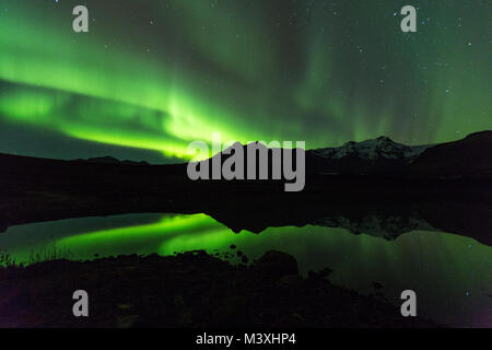 Green aurora light behind Lake mountain in iceland europe at national park skaftafell - Stock Photo
