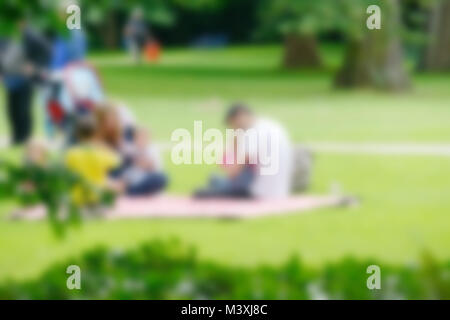 Blurred image of young family with children in summer park. - Stock Photo