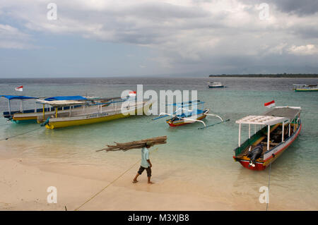 Scenic Landscape. Sunset at Gili Meno Island. Lombok, Indonesia.  Some boats on the shore of the beach in the eastern - Stock Photo