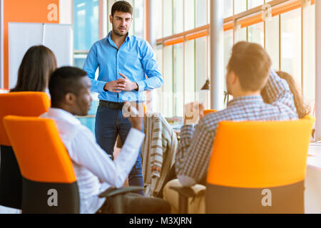Group of casually dressed businesspeople discussing ideas in the office. - Stock Photo