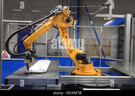 Industrial robotic arm in electronics production line - Stock Photo