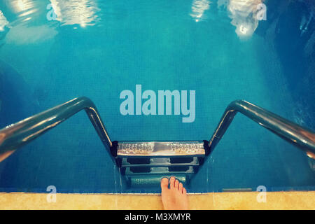 A person takes a step towards the water in the home swimming pool. legs with at the blue Swimming pool - Stock Photo