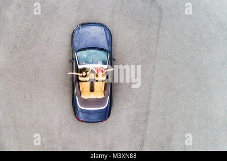 Small passenger sports convertible car with soft top down and happy couple of young women enjoying lifestyle and - Stock Photo