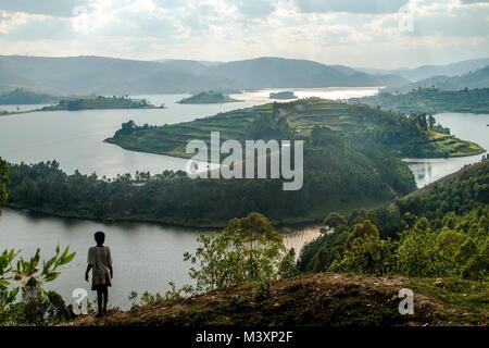 Ugandan girl looking out to Lake Bunyonyi, Uganda. - Stock Photo