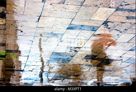 Blurry rainy day, a woman standing under red umbrella reflection silhouettes on wet city square  in high contrast - Stock Photo
