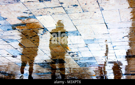 Blurry rainy day, people walking under umbrella reflection silhouettes on wet city square  in high contrast - Stock Photo
