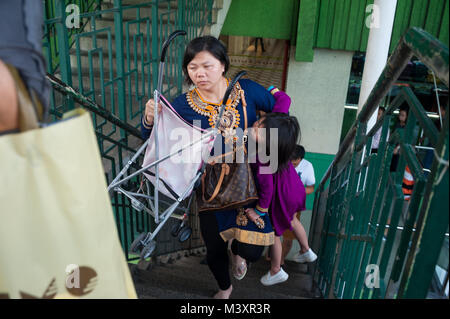 21.01.2018, Singapore, Republic of Singapore, Asia - A mother carries her daughter and a stroller as she walks up - Stock Photo