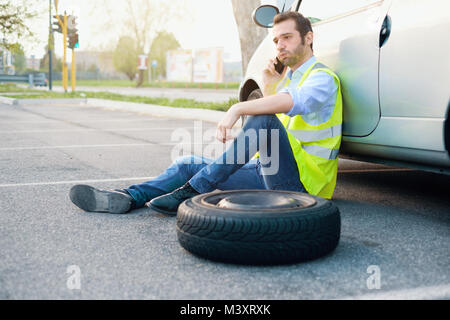 Man calling help service for a flat tyre after vehicle breakdown with smartphone - Stock Photo