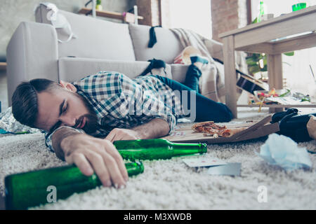 Sick drunk dreamy bearded guy clothed in checkered shirt and denim jeans is sleeping on the floor with an empty - Stock Photo