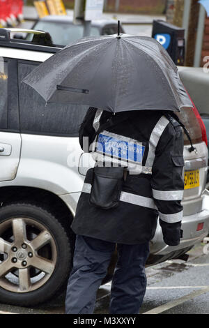 A traffic warden or civil enforcement office in a rain storm or checking vehicles and cars for tickets in the pouring - Stock Photo