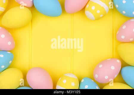Easter egg frame. Pink, yellow and blue colors on a bright yellow wood background. - Stock Photo
