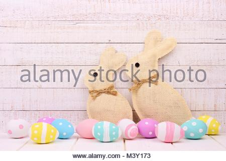 Rustic burlap Easter Bunnies with surrounding pastel eggs. Side view with a white wood background. - Stock Photo