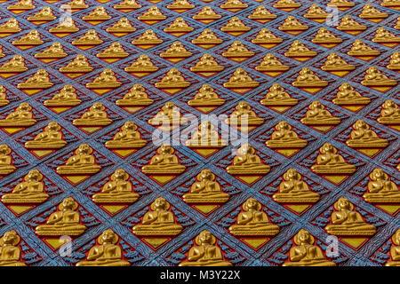 Wall of Buddhist monastery decorated with gilded Buddha statues. Reclining Buddha Wat Chaiyamangalaram. - Stock Photo