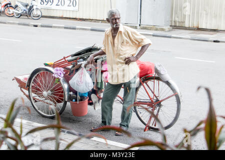 MALAYSIA, PENANG, NOV 14 2017, malaysian driver of rickshaw waits on the street for the passenger - Stock Photo