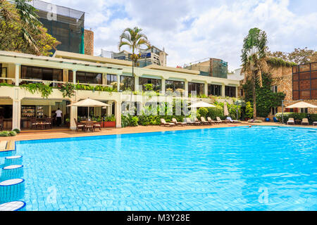 Outdoor blue water swimming pool and poolside bar area at the luxury 5 star Nairobi Serena Hotel, Nairobi, capital - Stock Photo