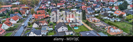 Aerial view of a suburb in Germany with detached houses, streets and gardens. New houses under construction, drone - Stock Photo