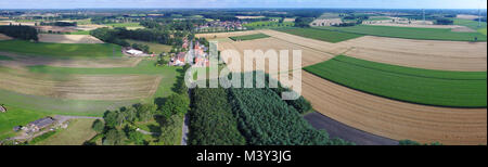Aerial view of fields, meadows and forests with a street in the middle and a small village in the background, drone - Stock Photo